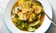 mexican chicken soup topped with tortillas and lime wedge
