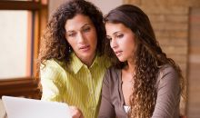 mom and teen daughter talking over laptop