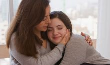 mom hugging teen daughter gray sweaters