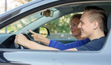 teen boy practicing driving with mom