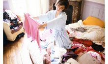 woman kneeling on bed among piles of clothes