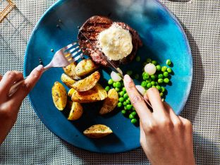 beef filet with blue cheese butter on top and potato wedges and peas on blue plate