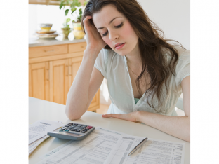 Woman looking frustrated at tax paperwork