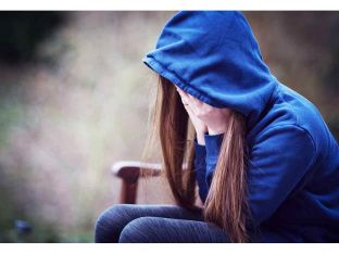 Teenage girl in hooded top with head in hands in despair