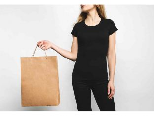 young woman in blank black t-shirt on white with shopping bag