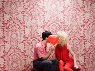 young couple behind a heart-shaped balloon