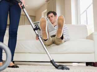 Man raising his feet while woman cleaning in living room