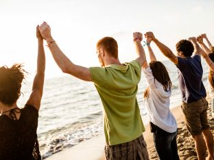 teen volunteers with arms raised on beach