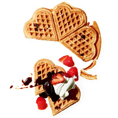 sweet heart waffles topped with strawberries chocolate syrup and whipped cream