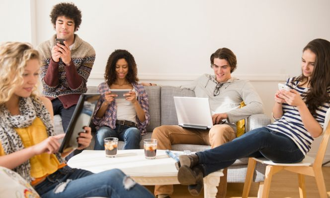 teens using devices in living room