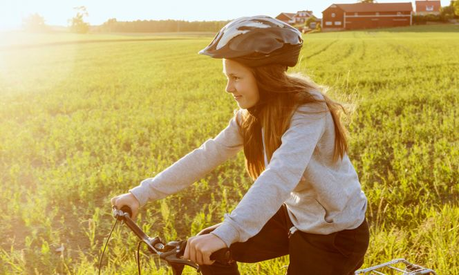 teen riding bike and wearing helmet