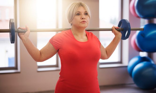 middle-age woman working out in red shirt