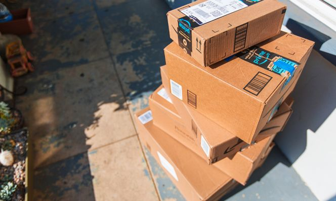 stack of amazon boxes on doorstep