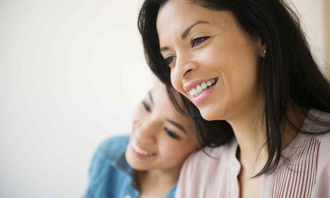 mother and teen daughter smiling together