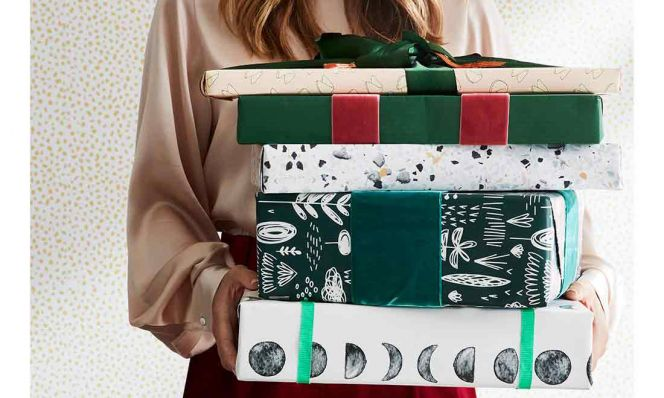 woman with a stack of wrapped christmas presents