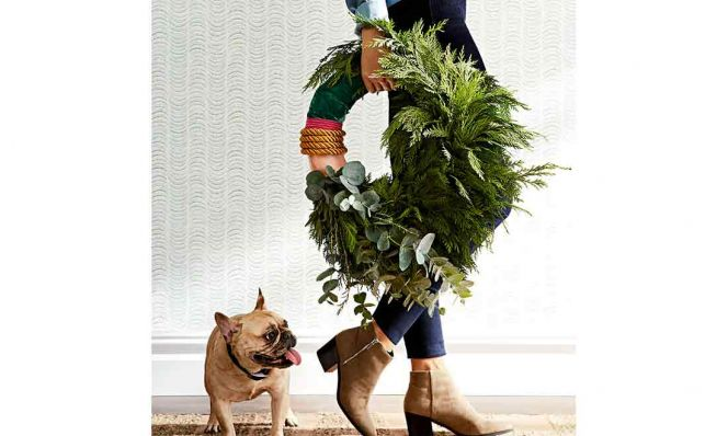 woman carrying a holiday wreath with dog watching