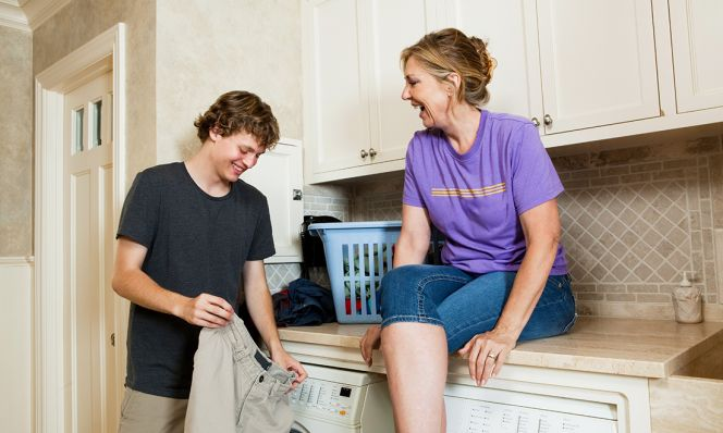 teen boy doing laundry while mother watches