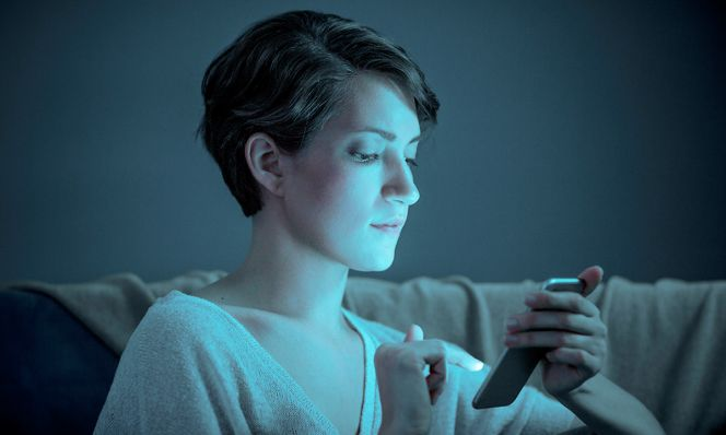 woman scrolling on phone in dark room