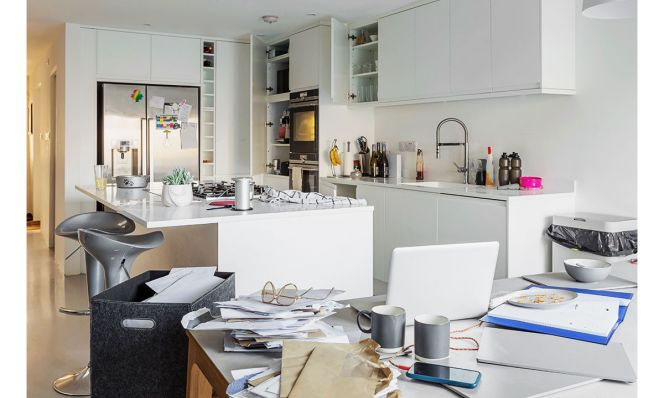 cluttered white kitchen with piles of mail